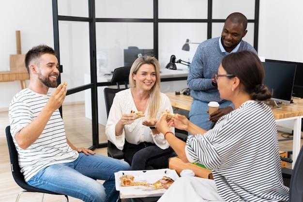 Młodzi szczęśliwi ludzie jedzą razem lunch