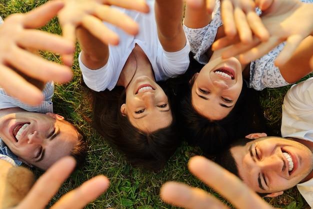 Młodzi szczęśliwi ludzie ma zabawę wpólnie w naturze