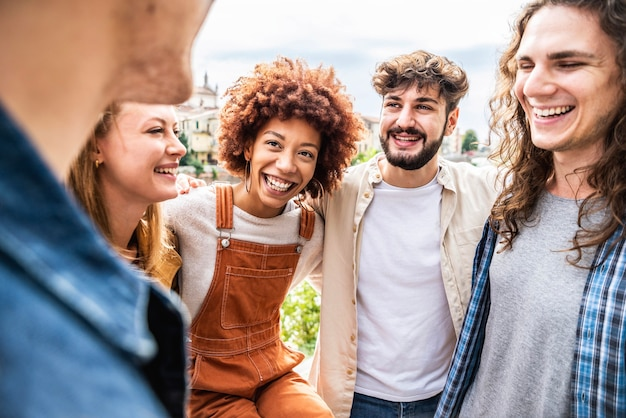Młodzi szczęśliwi ludzie śmieją się razem - wielorasowe grupy przyjaciół zabawy na ulicy miasta - portret studentów zróżnicowanej kultury doceniają poza - przyjaźń, społeczność, młodzież, koncepcja uniwersytetu.