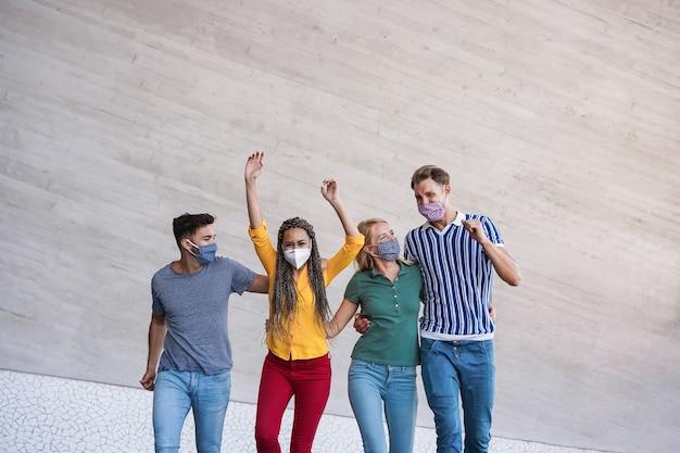 Młodzi szczęśliwi ludzie tańczą i bawią się podczas epidemii koronawirusa - skoncentruj się na twarzach