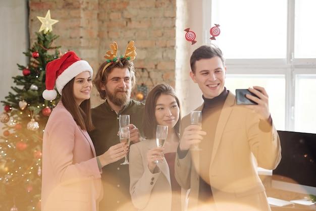 Młodzi, szczęśliwi pracownicy z kieliszkami szampana, patrzący w kamerę smartfona podczas robienia selfie podczas świątecznych toastów na imprezie biurowej