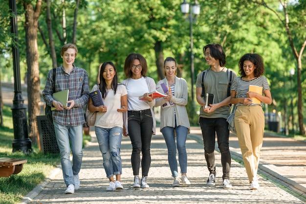 Młodzi szczęśliwi uczniowie chodzą podczas rozmowy. patrząc na bok.
