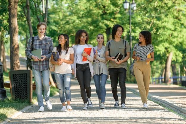 Młodzi szczęśliwi uczniowie chodzą podczas rozmowy