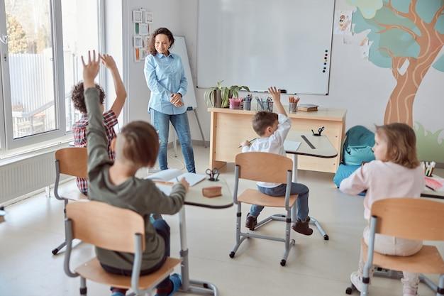 Młodzi szczęśliwi uczniowie szkoły podstawowej w lekkiej nowoczesnej klasie podnoszą ręce na lekcję