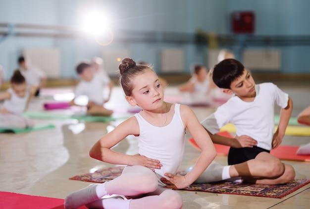 Młodzi tancerze w studiu baletowym. młodzi tancerze wykonują ćwiczenia gimnastyczne podczas rozgrzewki w klasie. sport, gimnastyka, rozwój dziecka