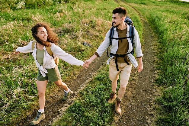 Młodzi turyści chodzą po polu