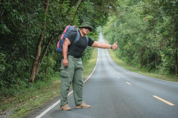 Młodzi turyści płci męskiej przewożących plecak do podróży autostopem. podróżuj autostopem. turyści czekają na autostop lub machanie o pomoc na poboczu drogi w lesie parku narodowego khao yai.