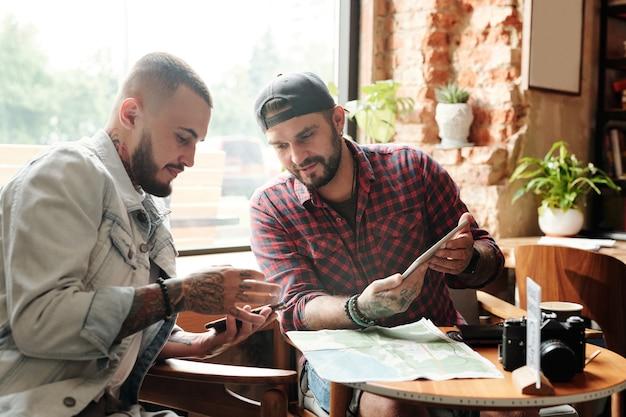 Młodzi turyści płci męskiej siedzą przy stole w kawiarni i sprawdzają mapę online na gadżetach, przygotowując się do podróży