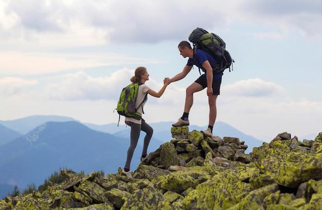 Młodzi turyści z plecakami, wysportowany chłopiec pomaga szczupłej dziewczynie wspinać się po skalistym szczycie góry na tle jasnego nieba i pasma górskiego