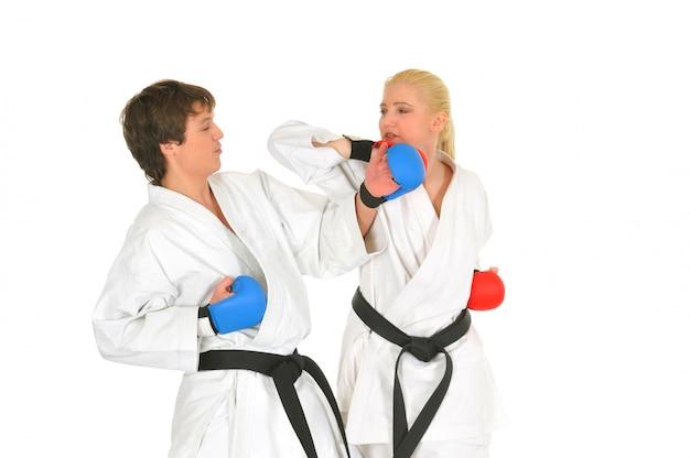 Młodzi uczniowie karateka w białym kimonie