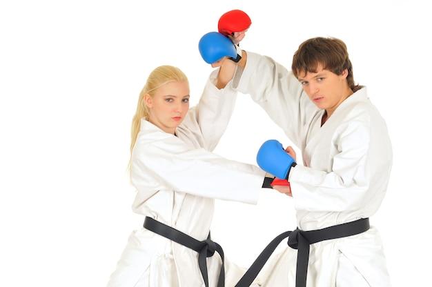 Młodzi uczniowie karateki w białych czarnych pasach kimono w rękawicach bojowych trenują ciosy kopaniem i rękami na białym tle
