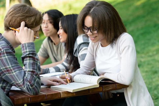 Młodzi uczniowie siedzący i studiujący na zewnątrz podczas rozmowy