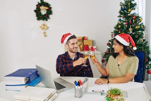 Młodzi uśmiechnięci koledzy świętują boże narodzenie w biurze i opiekania kieliszkami do szampana