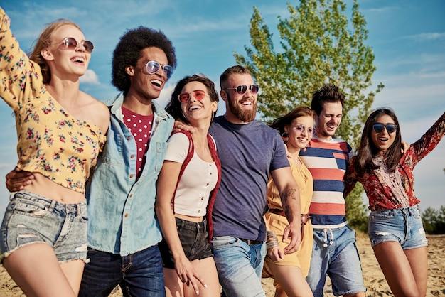 Młodzi uśmiechnięci ludzie z rzędu na świeżym powietrzu