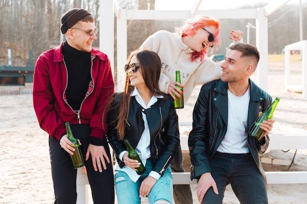 Młodzi uśmiechnięci przyjaciele pije piwo wpólnie