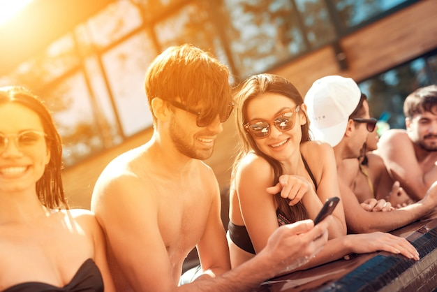 Młodzi uśmiechnięci przyjaciele używa smartphone przy poolside