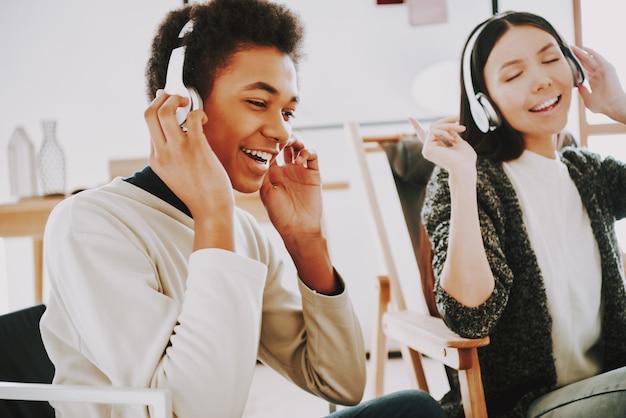 Młodzi uśmiechnięci twórcy słuchają muzyki w słuchawkach.
