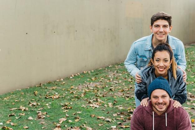 Młodzi uśmiechnięci wielorasowi przyjaciele stojący jeden za drugim