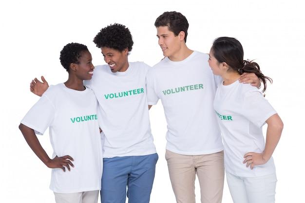Młodzi uśmiechnięci wolontariuszi patrzeje kamerę