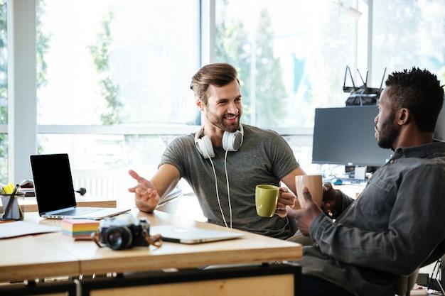 Młodzi wesoły koledzy siedzący w biurze rozmawiają ze sobą