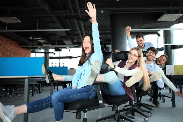 Młodzi, wesoły ludzie biznesu w eleganckich ubraniach na co dzień bawią się podczas wyścigów na krzesłach biurowych i uśmiechają się.