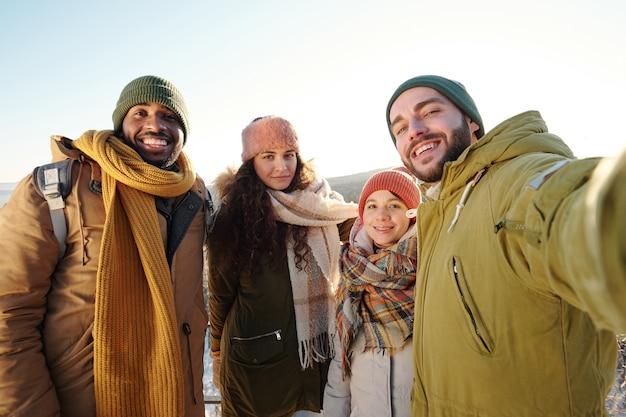 Młodzi wesoły międzykulturowi przyjaciele w odzieży zimowej robiący selfie przed kamerą na tle jasnego nieba w słoneczny zimowy dzień podczas relaksu
