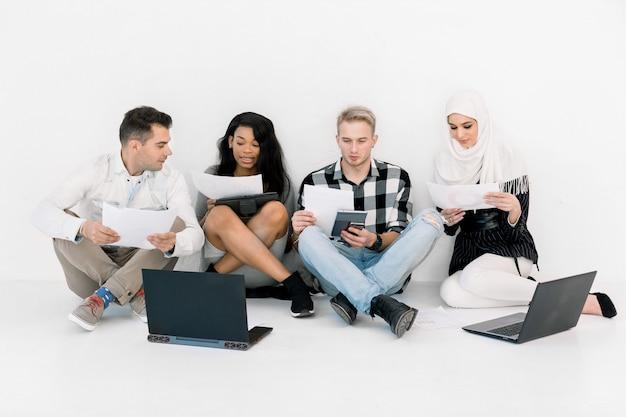 Młodzi wieloetniczni ludzie pracujący na laptopie i tablecie przy nowym kreatywnym projekcie i burzy mózgów, siedzący na podłodze na białym