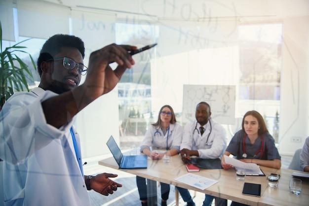 Młodzi wieloetniczni stażyści słuchają wykładu afroamerykańskiej lekarki na konferencji medycznej w klinice