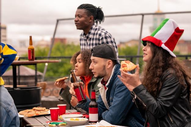 Młodzi wielokulturowi kibice piłki nożnej w codziennych ubraniach piją pizzę i piwo podczas oglądania transmisji na świeżym powietrzu