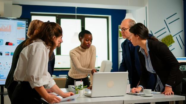 Młodzi wielokulturowi pracownicy grupują się, rozmawiając, patrząc na laptopa i analizując dane cyfrowe siedząc przy biurku w miejscu pracy. zespół profesjonalnych kolegów omawianie projektu za pomocą urządzeń w biurze firmy.