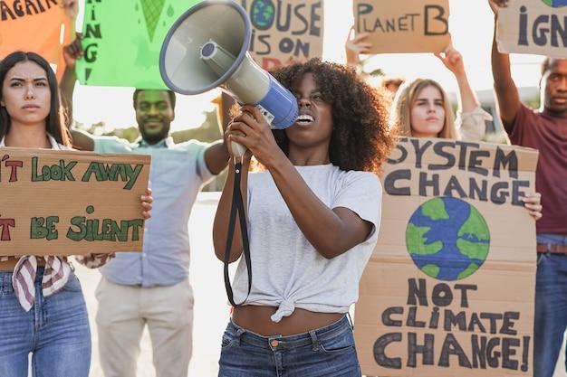 Młodzi, wielorasowi ludzie demonstrują na ulicy z transparentem na rzecz zmian klimatycznych. pokolenie milenijne walczące o przyszłą katastrofę klimatyczną