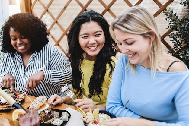 Młodzi wielorasowi ludzie jedzą śniadanie na świeżym powietrzu w restauracji na patio - skoncentruj się na twarzy azjatyckiej dziewczyny girl