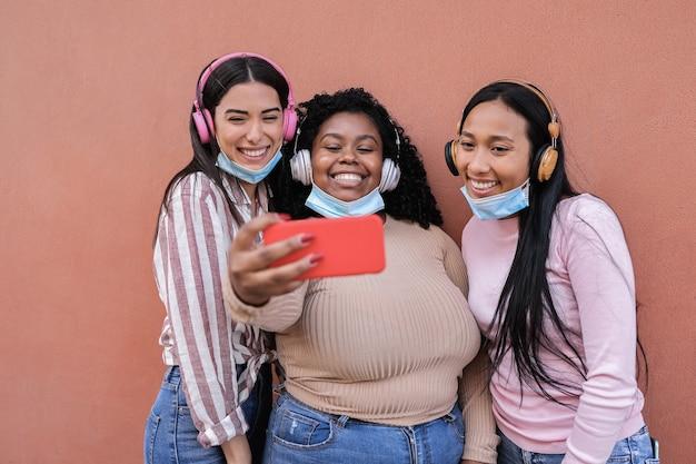 Młodzi wielorasowi ludzie noszący maski ochronne podczas robienia selfie z telefonem komórkowym na zewnątrz - główny nacisk na dziewczynę z centrum