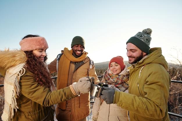 Młodzi wielorasowi ludzie w zimowych strojach brzęczących kubkami gorących napojów