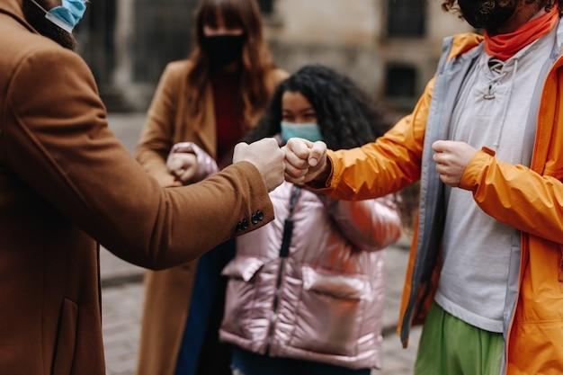 Młodzi wielorasowi ludzie witają się pięściami, stojąc na zewnątrz. przyjaciele w maskach medycznych korzystający z nowej alternatywy na spotkanie podczas koronawirusa.