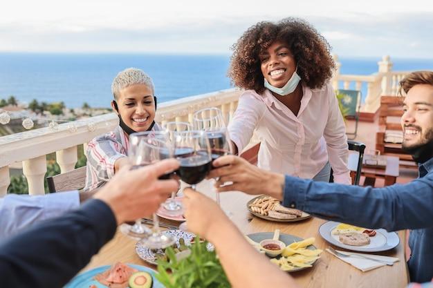 Młodzi wielorasowi ludzie wiwatujący przy winie i jedzący z maskami pod brodą w restauracji na patio - skoncentruj się na twarzy afrykańskiej kobiety