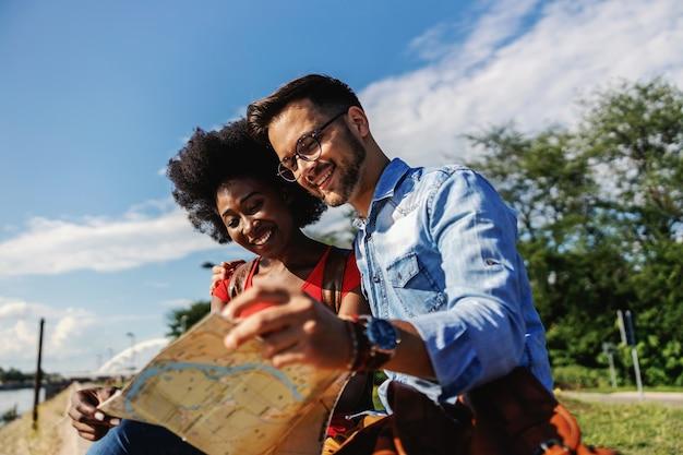 Młodzi wielorasowi turyści siedzący na świeżym powietrzu i eksplorujący mapę.