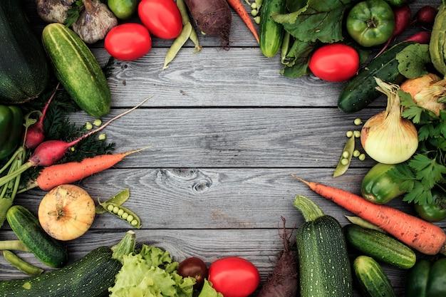 Młodzi wiosen warzywa na drewnianym chalkboard od above