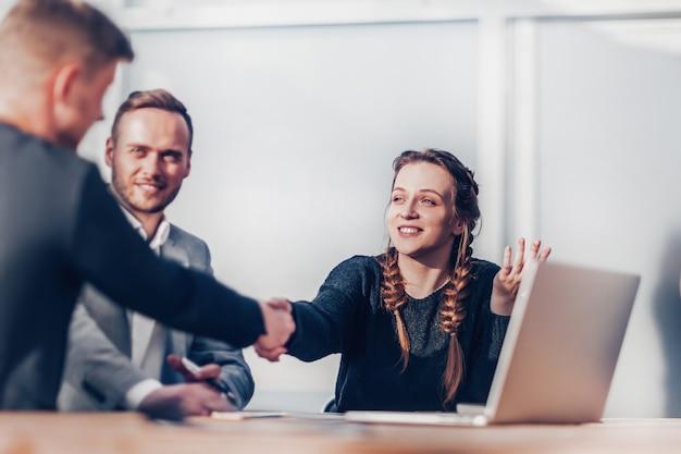 Młodzi współpracownicy ściskają sobie ręce na spotkaniu grupowym