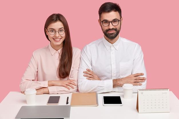 Młodzi współpracownicy siedzący przy biurku z gadżetami i kalendarzem