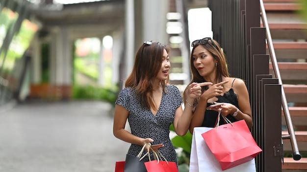 Młodzi zakupy przyjaciele chodzi na kurortu centrum handlowego
