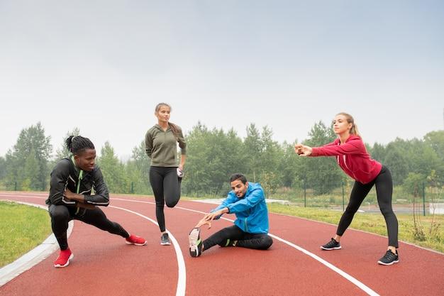 Młodzi, zdrowi międzykulturowi mężczyźni i kobiety w strojach sportowych wykonujący ćwiczenia fizyczne na stadionie zewnętrznym