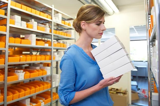 Młodzi żeńscy farmaceuty mienia pudełka