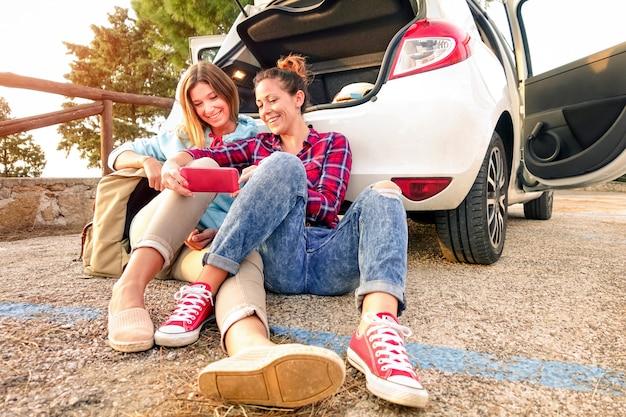Młodzi żeńscy najlepsi przyjaciele ma zabawę z mobilnym mądrze telefonem w samochodowej wycieczki momencie