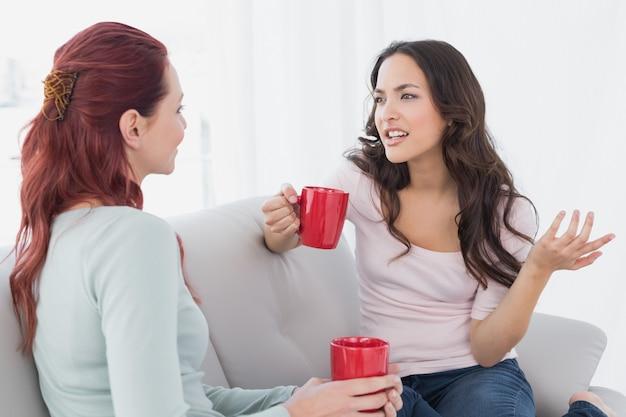 Młodzi żeńscy przyjaciele cieszy się gadkę nad kawą w domu