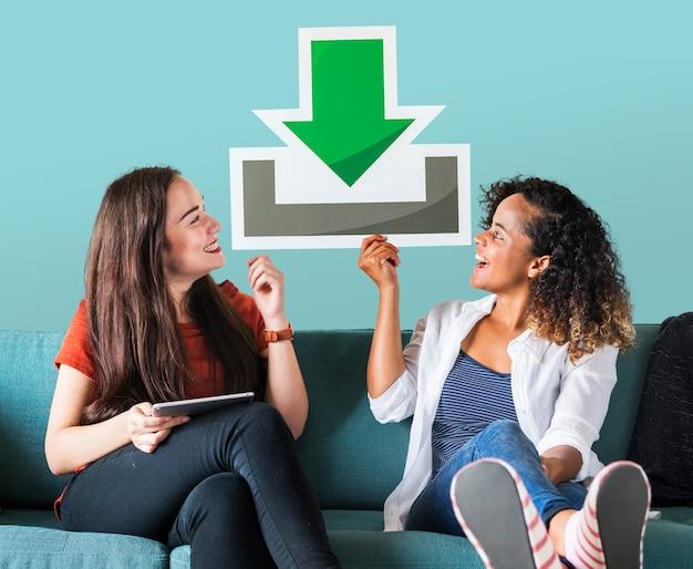Młodzi żeńscy przyjaciele trzyma ściąganie ikonę