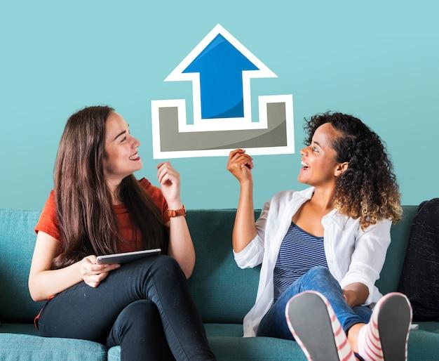 Młodzi żeńscy przyjaciele trzyma upload ikonę