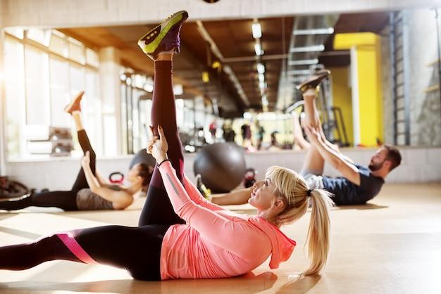 Młodzi zmęczeni sportowcy na siłowni rozciągają mięśnie nóg po zajęciach pilates.