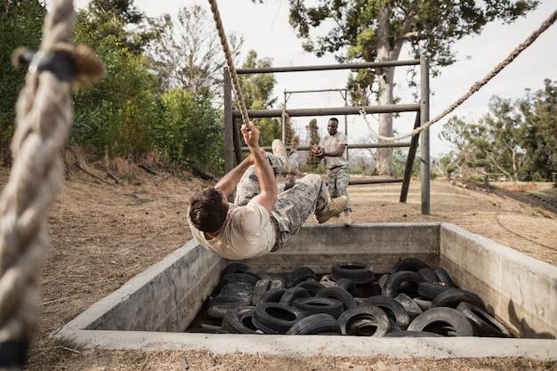 Młodzi żołnierze ćwiczący wspinaczkę linową na torze przeszkód na obozie treningowym