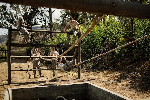 Młodzi żołnierze ćwiczący wspinaczkę linową na torze przeszkód